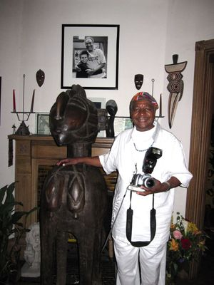 Poet Eugene Redmond with a Nimba statue from the Baga people of Guinea.