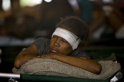 A Haitian girl rests after receiving treatment at an ad hoc medical clinic in the aftermath of the Haitian earthquake.