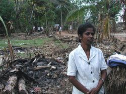 Mrs. C. Vinita of Belliwate village not only lost her home in the tsunami, but also her daughter, who was getting ready to write her A-level exam. She stands in front of property flattened by the tsunami.