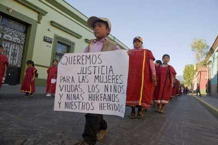 A Triqui boy carries a sign that says, We want justice for the widows, the orphans and our injured.