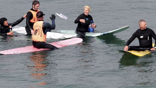 Photo by Shmuel Thaler of the Santa Cruz Sentinel of Vice Mayor Hilary Bryant delivering books to surfers