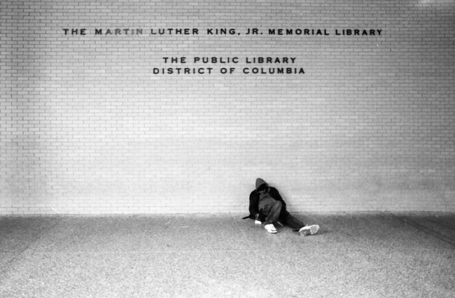 Man sitting at MLK Jr. Memorial Library, courtesy of Alexander Barth via Wikimedia Commons