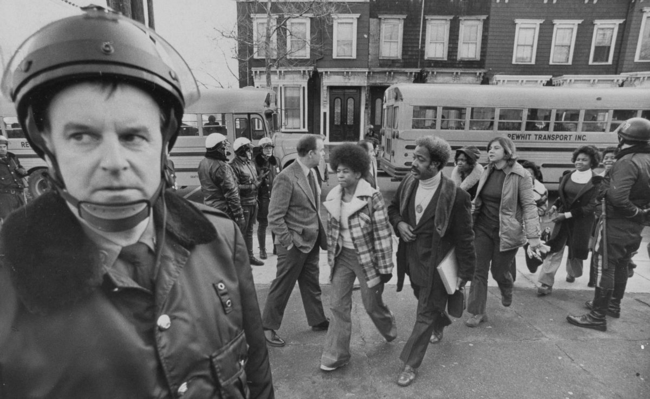 Buses arrive at South Boston High School, Jan. 8, 1975, as classes resume at the racially troubled institution. Police were on hand to provide protection as black students arrived. (AP)