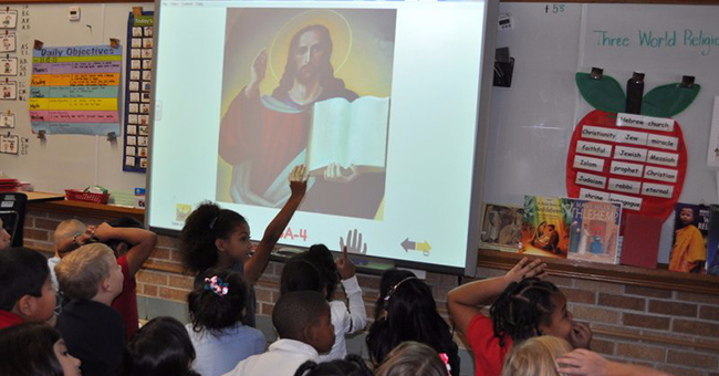 Children in a first-grade class in Wichita, KS field questions from their teacher in a lesson about the origins of Christianity as part of a unit on three world religions: Judaism, Christianity, and Islam.