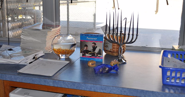 A Hanukkah menorah, dreidel, Hanukkah gelt, and children's book on Passover on display during a world religions unit on Judaism, Wichita, KS.