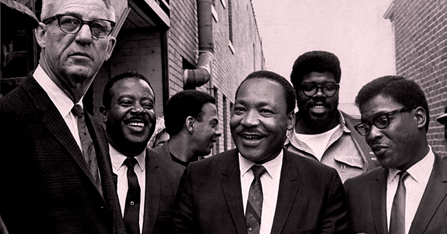 As US Marshal Cato Ellis serves an injunction on MLK, King and his aides (l to r), Ralph Abernathy, Andrew Young, James Orange and Bernard Lee, share a laugh to lighten the mood.