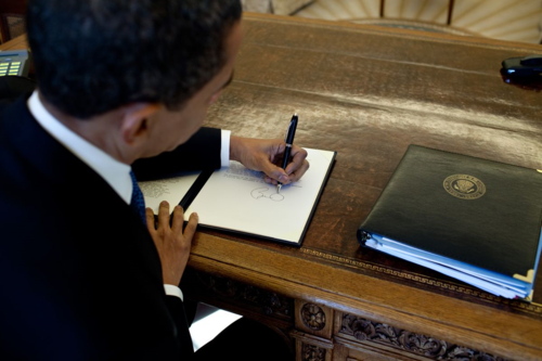 Obama signs at his desk