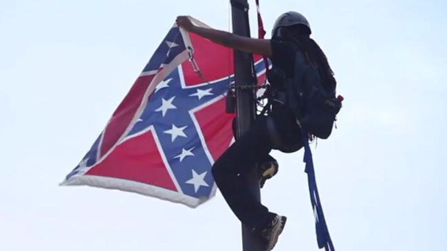 Bree Newsome scaling the flagpole