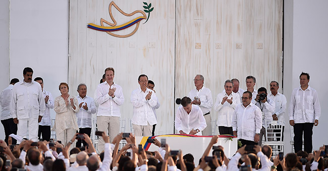 Colombian President Juan Manuel Santos signing the peace agreement with FARC leader Timochenko