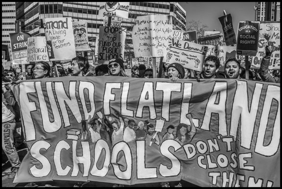 Teachers and community members march behind a banner opposing the closure of 24 schools, which targets schools in the Oakland flatlands, predominantly low-income communities of color.