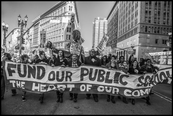 The strikers march behind their banner down Broadway in downtown Oakland